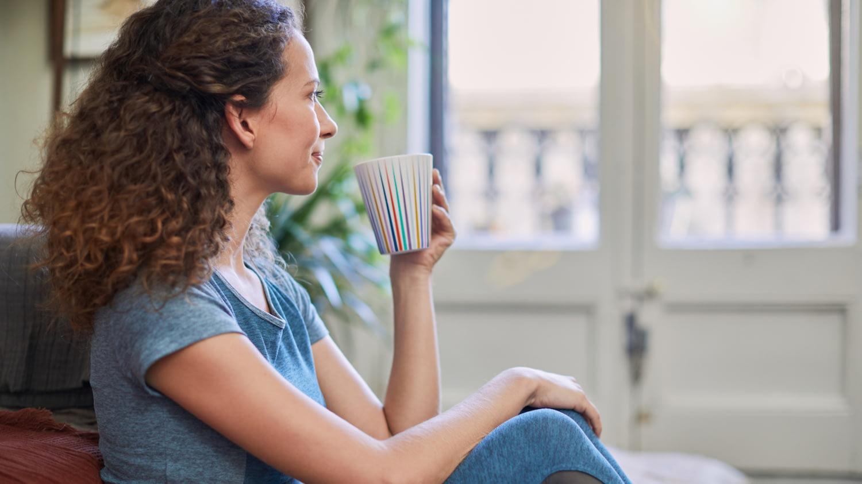 Eine junge Frau sitzt entspannt mit einem Becher Kaffee auf ihrem Sofa