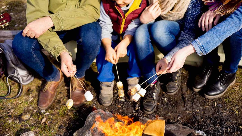 Eine Familie sitzt um ein Lagerfeuer und grillt Marshmallows