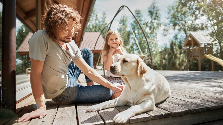 Vater und Tochter sitzen mit Hund auf einer Veranda