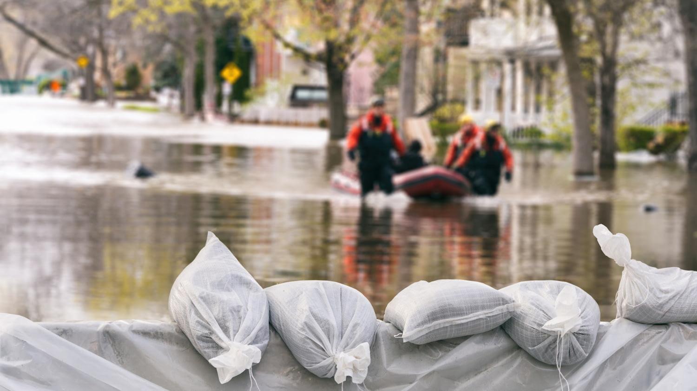 Sandsäcke im Vordergrund sollen Häuser schützen, dahinter ein Schlauchboot mit Helfern auf einer überschwemmten Straße