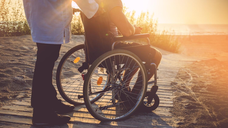 Ein Pfleger schiebt einen jungen Mann im Rollstuhl zu einem Strand.