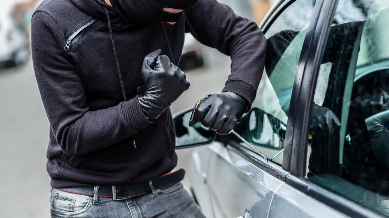 Mann setzt Schraubenzieher an, um in ein Auto einzubrechen.