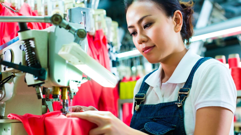 Chinesische Frauen sitzen in einer Textilfabrik und nähen