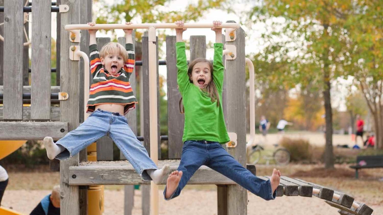 Ein Junge und ein Mädchen lassen sich auf einem Abenteuerspielplatz vom Klettergerüst hängen und strecken die Zungen heraus