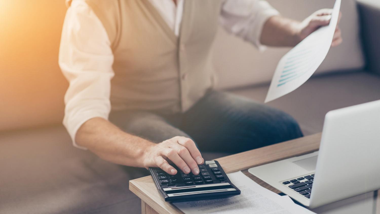Auszahlung betriebliche Altersvorsorge: Ein Mann sitzt mit Taschenrechner und Laptop am Tisch und berechnet etwas.