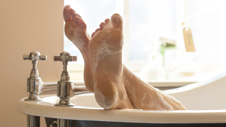 Zwei schaumbedeckte Füße ragen neben angesagten Retro-Armaturen aus einer freistehenden Badewanne.