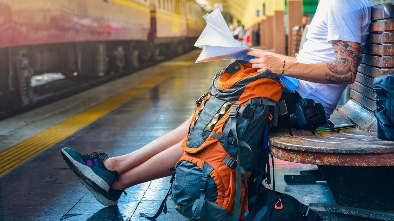 Ein Mann sitzt mit einem großen Rucksack auf einer Bank an einem Bahngleis.
