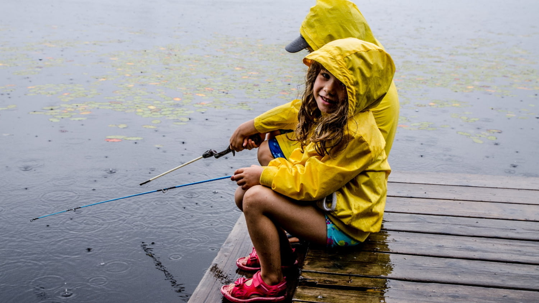 Zwei Kinder angeln bei Regen am See