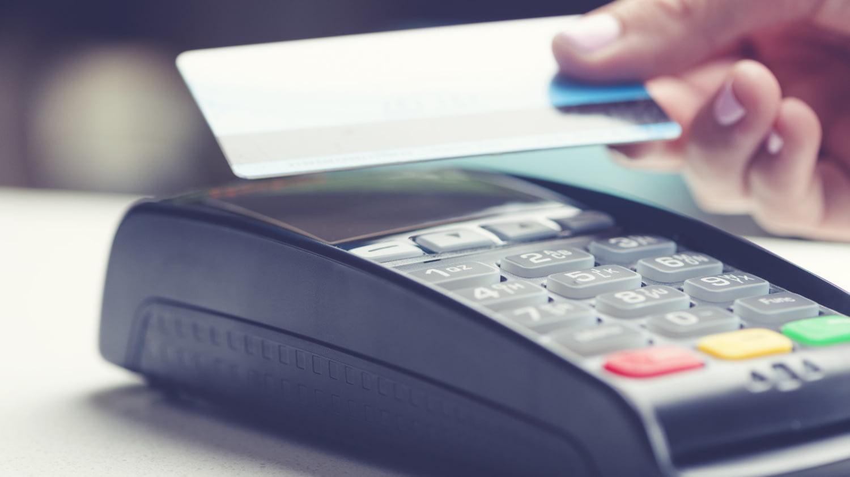Eine Hand hält eine Kreditkarte dicht vor ein Lesegerät