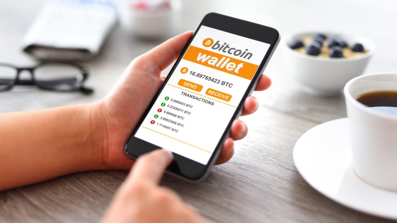Hand tippt auf einer Wallet-App auf dem Smartphone