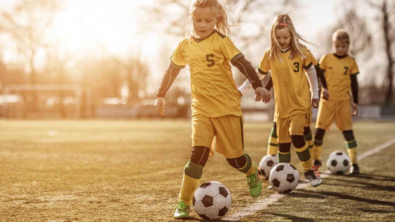 Junge Mädchen laufen beim Fußballtraining mit je einem Ball an der Außenlinie entlang