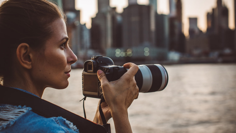 Frau blickt auf Skyline mit Kamera in der Hand