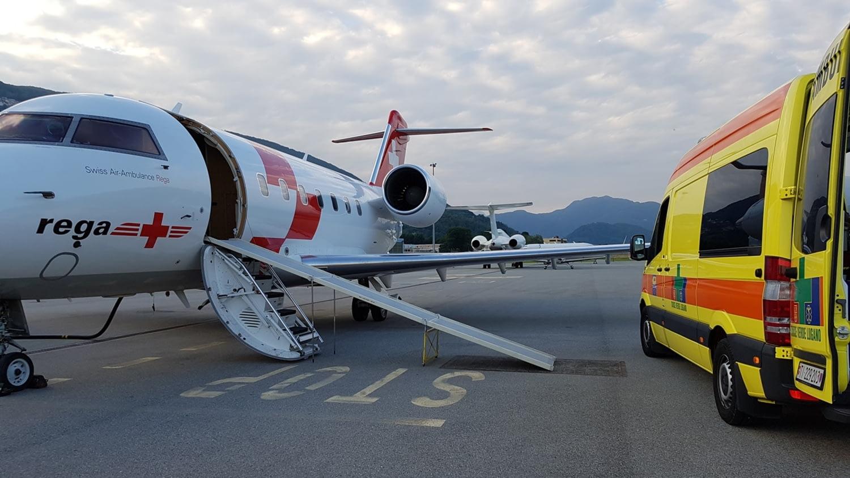 Schweizer Ambulanzflugzeug und ein Rettungswagen aus einem Rollfeld vor Alpenpanorama.