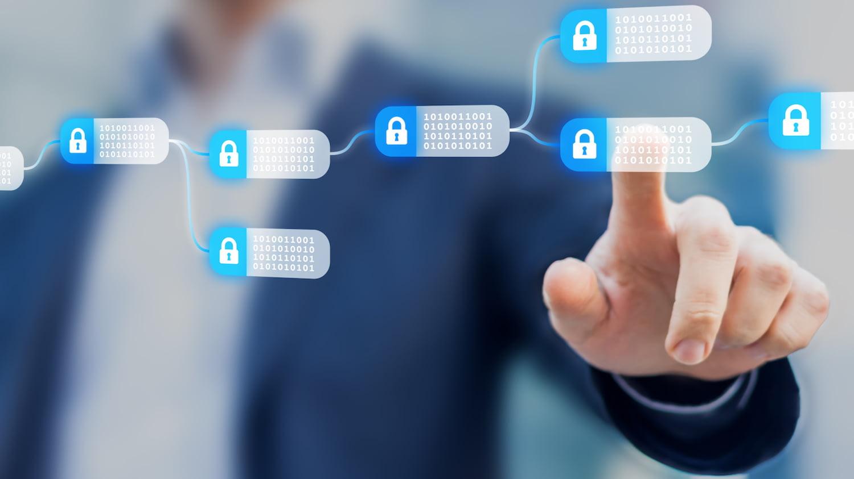 Symbolbild Blockchain: Eine Männerhand zeigt auf einen Bildschirm mit mehreren verknüpften und verschlüsselten Datenblöcken