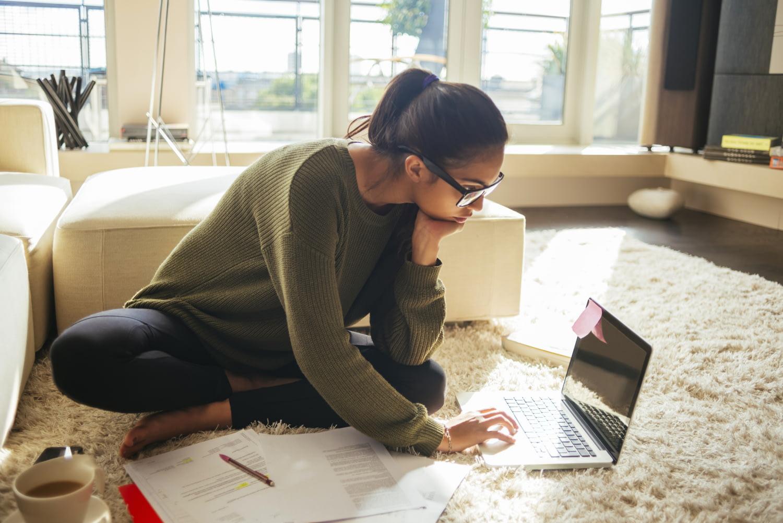 Junge Frau sitzt im Schneidersitz auf dem Boden zwischen verschiedenen Dokumenten und tippt einen Brief in ihren Laptop.