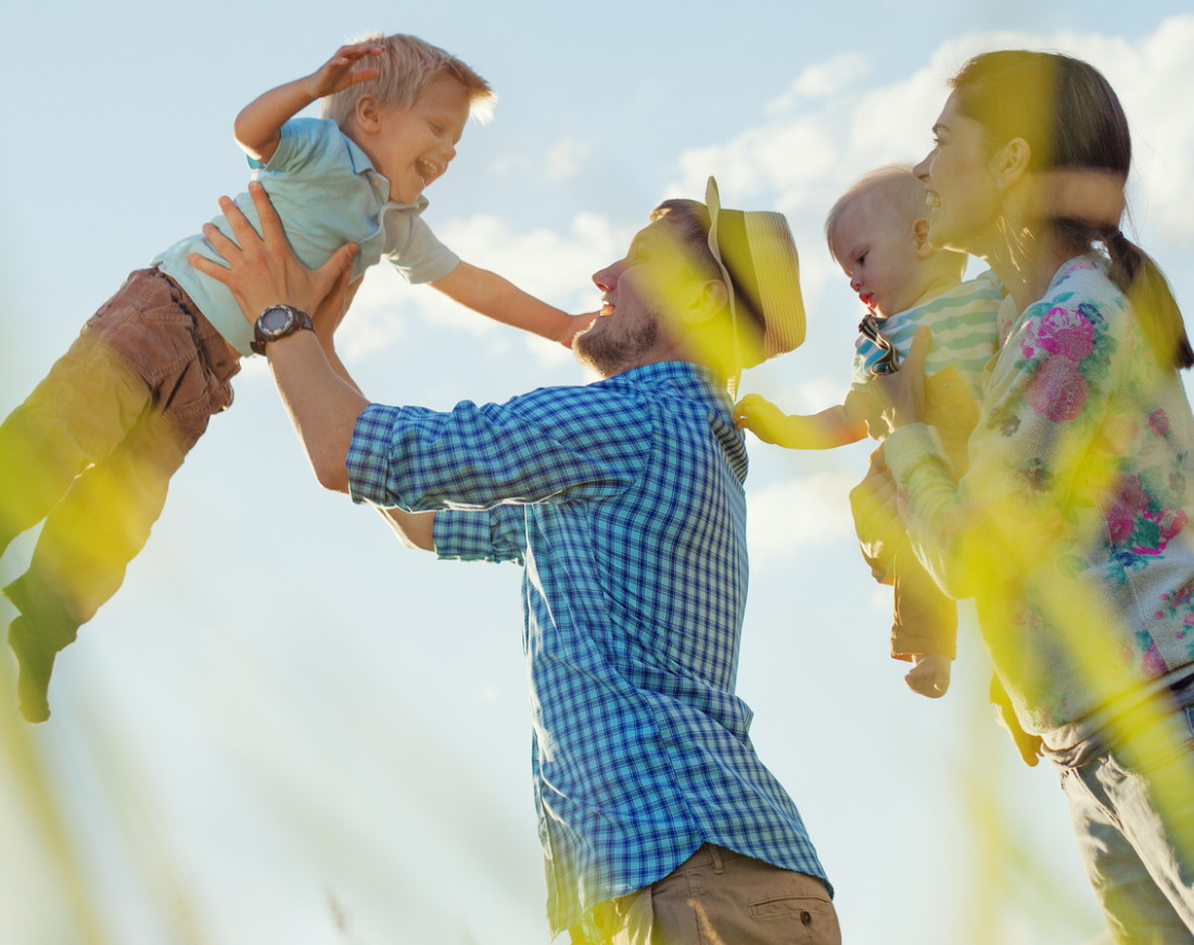Eltern spielen vor blauem Himmel mit ihren Kindern, der Vater hält den Sohn hoch in die Luft