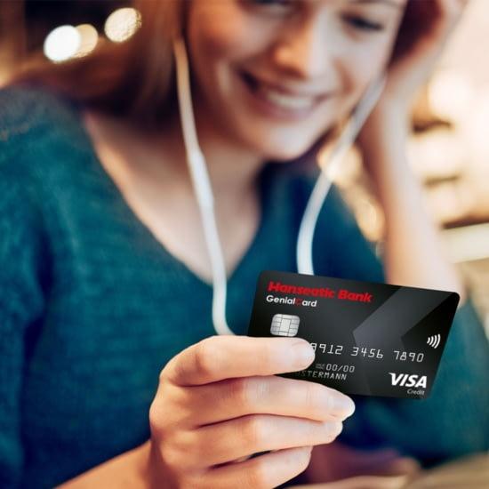 Frau mit GenialCard in der Hand, die kostenlose VISA Kreditkarte der Hanseatic Bank