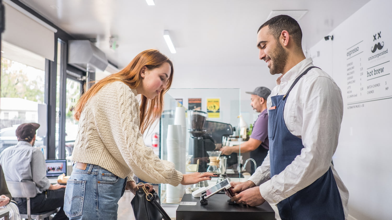 Junge Frau zahlt per Kreditkarte in einem amerikanischen Coffee-Shop