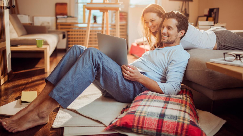 Pärchen schaut gemeinsam auf Computerbildschirm, um die Inhalte seines Smart Contracts zu prüfen