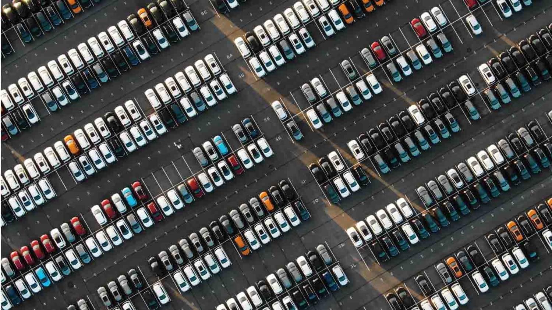 Luftaufnahme von einem Parkplatz mit Dutzenden Neuwagen