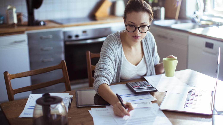 Junge Frau berechnet mit Taschenrechner und Laptop ihren Selbstbehalt