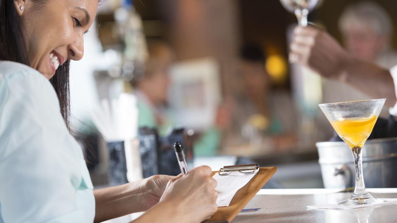 Eine junge Frau sitzt im Restaurant und unterschreibt ihre Rechnung für die Kreditkartenzahlung