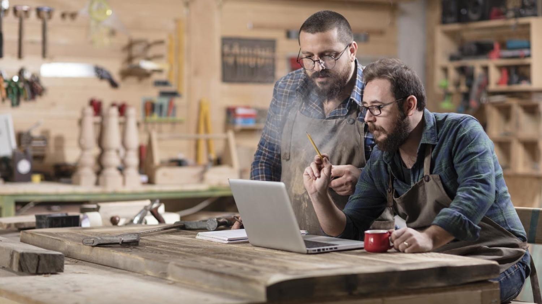 Zwei Schreiner sitzen in ihrer Werkstatt vor einem Laptop