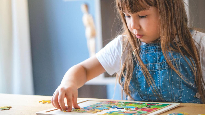 Ein Mädchen setzt ein Puzzle zusammen
