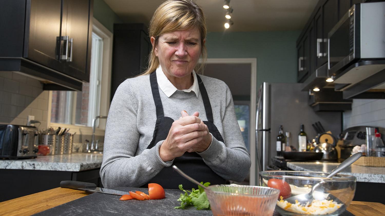 Frau hat sich beim Kochen in den Finger geschnitten