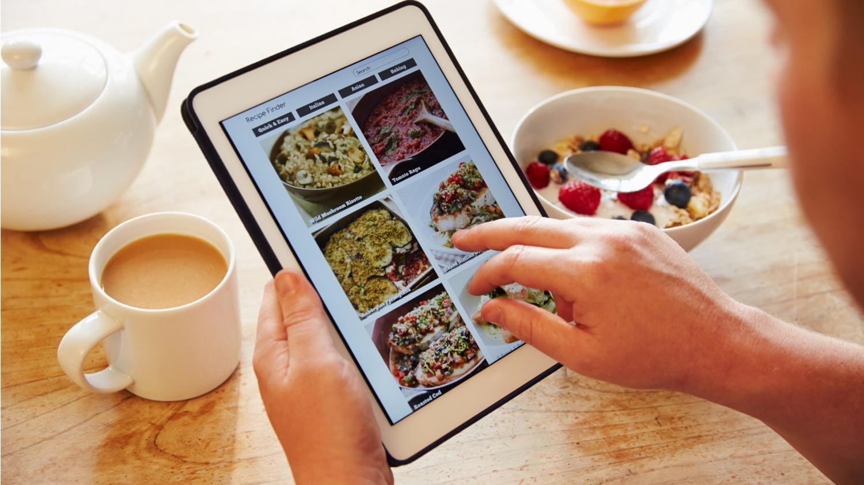 Eine Hand wischt über ein Tablet, auf dem verschiedene Rezepte zu sehen sind.