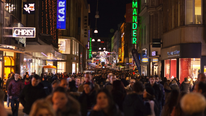 Viele Menschen beim abendlichen Shopping in einer Fußgängerzone