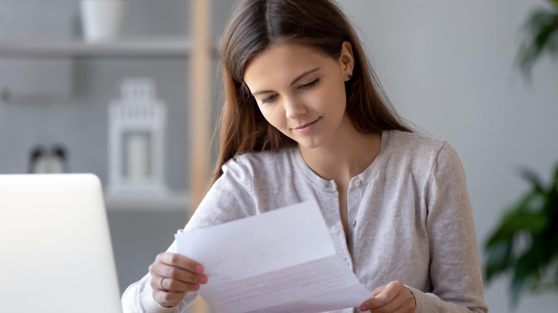 Eine junge Frau liest in einem Dokument