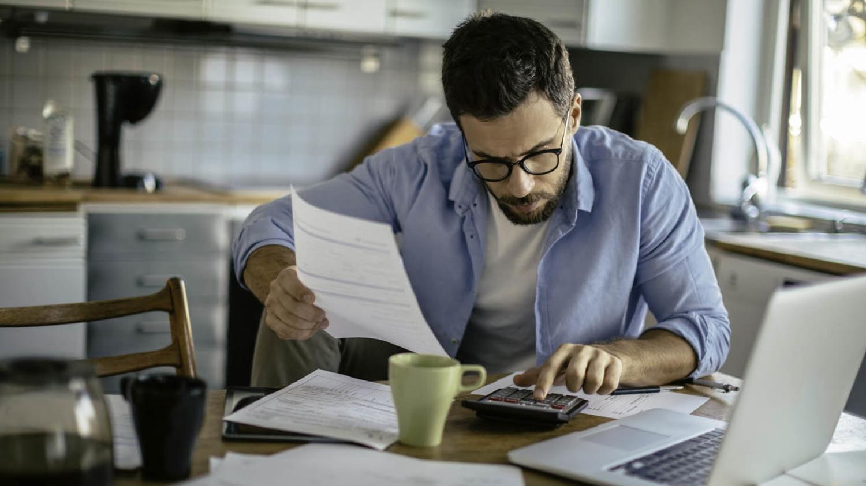Mann geht am Küchentisch Rechnungen durch und tippt auf einem Taschenrechner