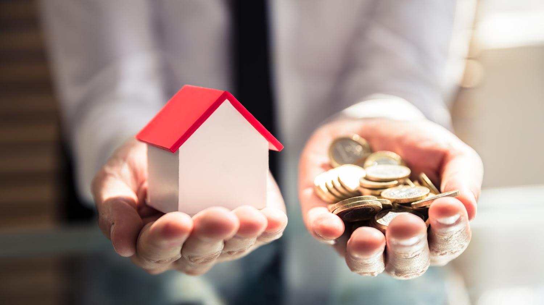 Zwei ausgestreckte Hände – eine hält ein Modell eines Hauses, die andere ist voller Münzen.