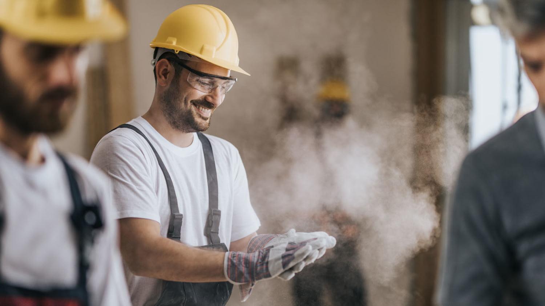 Zufrieden lächelnder Handwerker klopft Baustaub aus seinen Arbeitshandschuhen