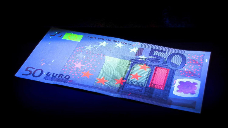 Ein Geldschein liegt in dunkler Umgebung und wird mit UV-Licht angestrahlt