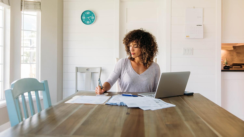 Frau sitzt mit Laptop und Papieren am Tisch und schreibt etwas auf einen Notizblock