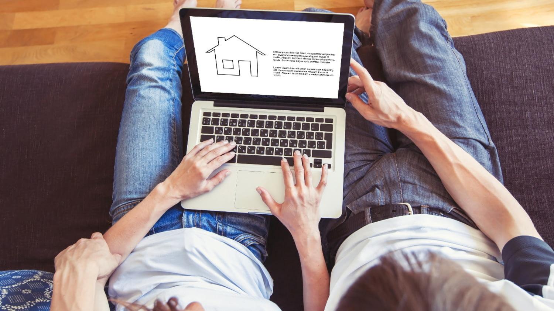 Ein Paar sitzt auf dem Sofa und sieht sich auf dem Laptop die Zeichnung eines Hauses an