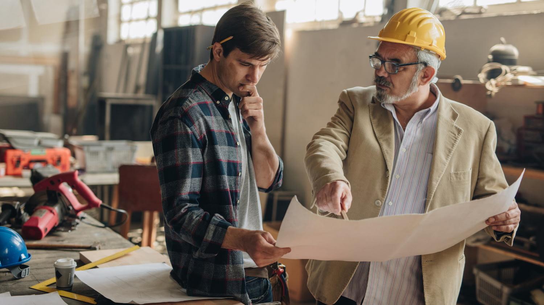 Zwei Handwerker diskutieren in einer Werkstatt über einen Plan, den einer von ihnen in der Hand hält.