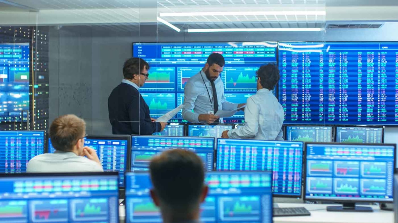 Börsenhändler zwischen vielen Monitoren, die Zahlen und Grafiken zeigen