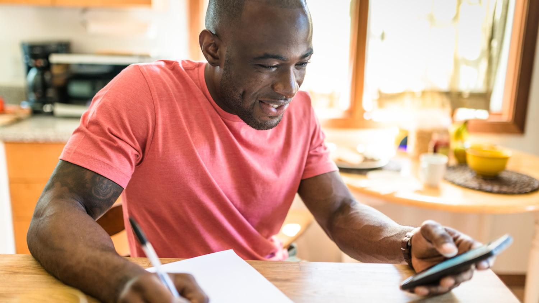 Ein junger Mann sitzt zu Hause an einem Tisch, schreibt mit der rechten Hand einen Text und bedient mit der linken ein Smartphone