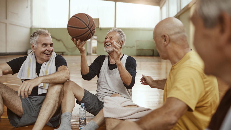 Eine Gruppe Senioren ruht sich nach einer Runde Basketball auf dem Boden einer Sporthalle aus