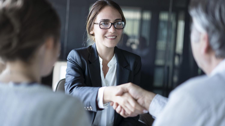 Junge Frau im Business-Outfit und ein Mann mittleren Alters besiegeln eine geschäftliche Absprache per Handschlag