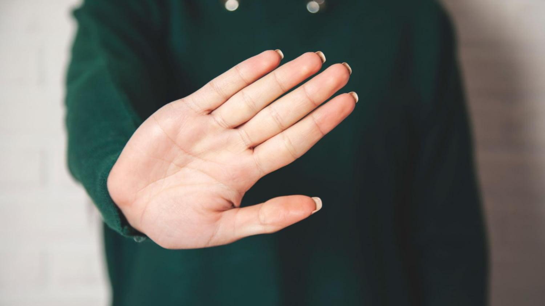 Eine Frau zeigt offene Handfläche als Zeichen der Ablehnung