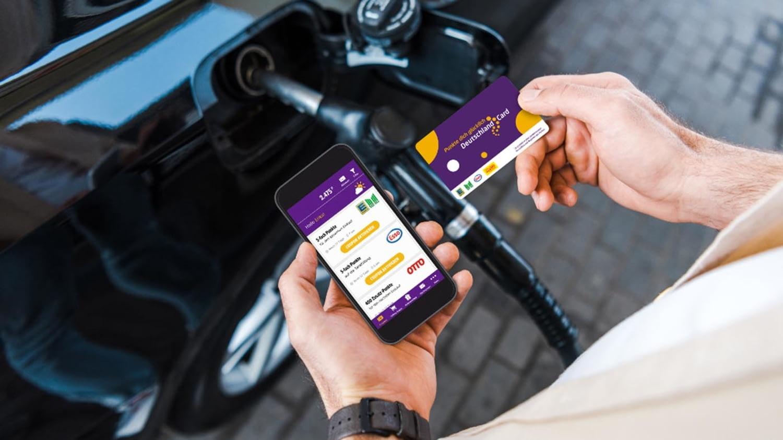 Beim Tanken hält ein Mann sowohl ein Smartphone mit der DeutschlandCard-App als auch die Karte in den Händen
