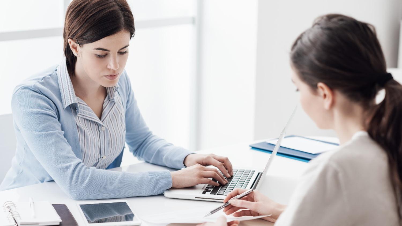 Zwei junge Frauen sitzen sich an einem Schreibtisch gegenüber. Eine tippt auf einem Laptop, die andere zeigt etwas auf einem Schriftstück