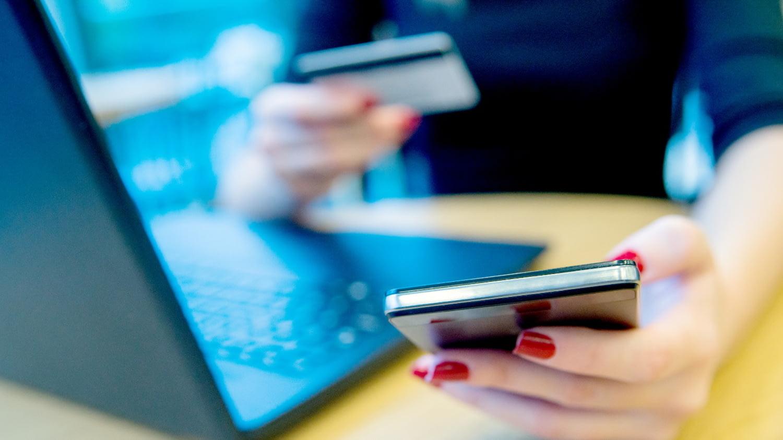 Eine Damenhand tippt in Großaufnahme auf dem Smartphone vor einem Laptop, die andere hält eine Kreditkarte.