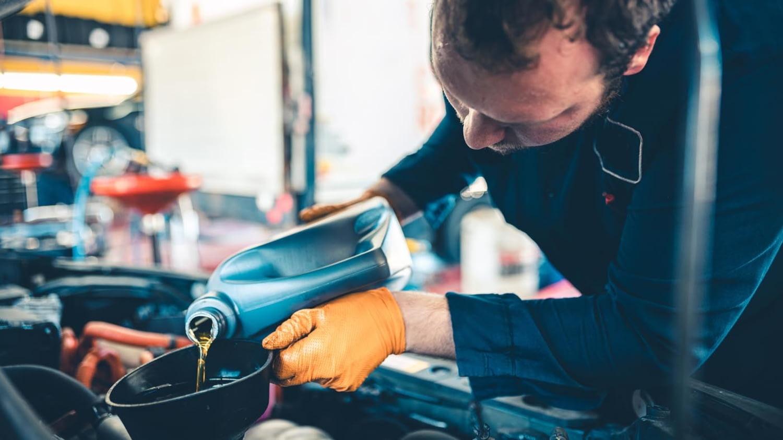 Automechaniker füllt Motoröl nach