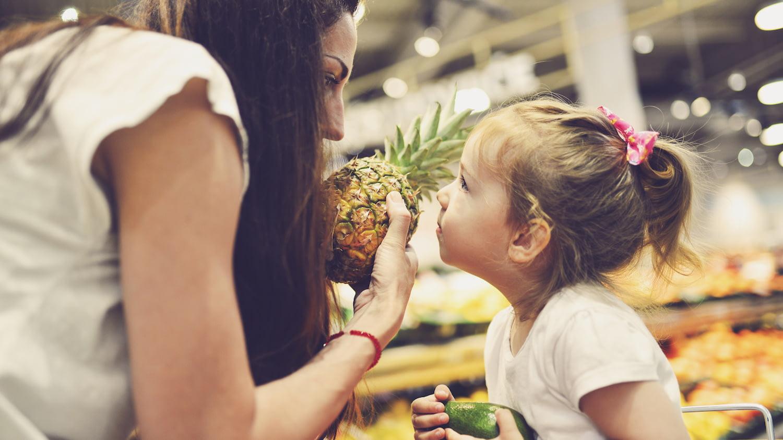 Mutter zeigt Tochter im Supermarkt eine Ananas