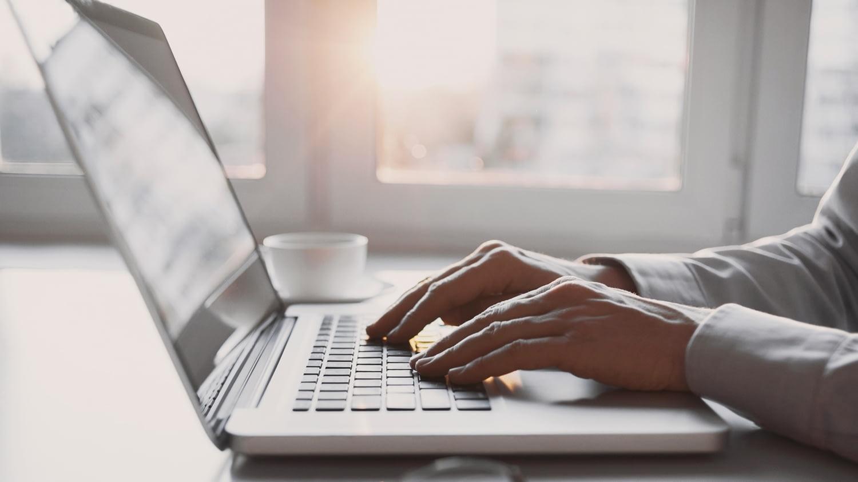 Ein Mann schreibt auf seinem Laptop